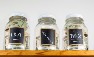 Three Glass Jars On Wooden Shelf For Savings